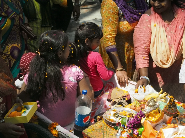 Children throw flowers and coloured flour to celebrate the deity Ganesha.