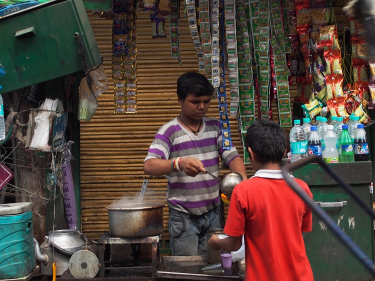 A child serves street food to another child in Old Delhi.